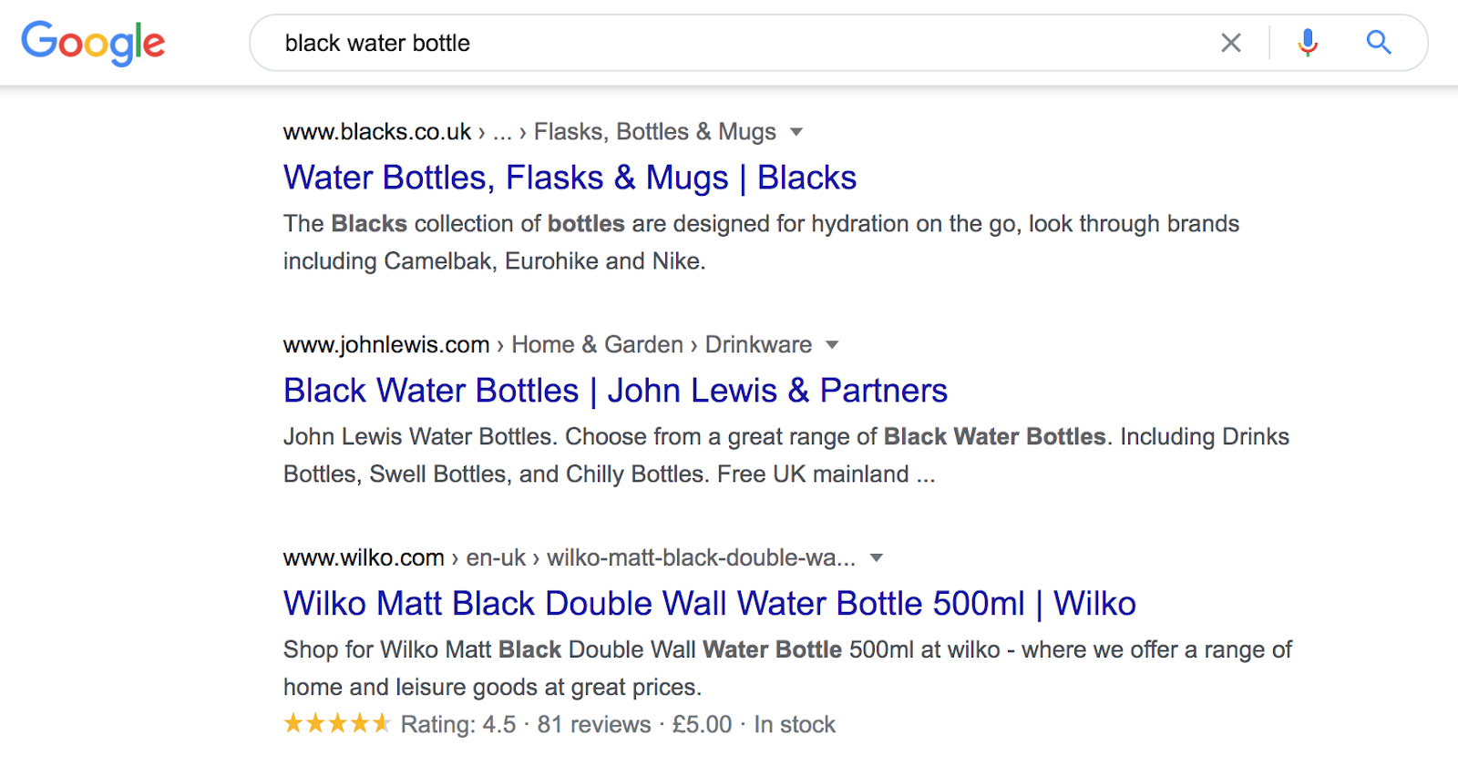 """The image shows a Google search page, with the text """"black water bottle"""" written in the search bar. The first result is from blacks.co.uk website and the title reads """"Waterbottles flasks & mugs"""". The second result is from John Lewis.com and reads """"Black water bottles"""". The third result is from Wilko.com and reads """"Wilko matt black double wall water bottle"""". Under this text, there are 4,5 yellow stars and the copy """"Rating: 4.5 - 81 reviews""""."""