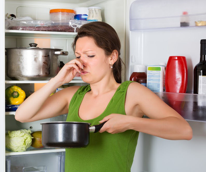 A woman holding her nose at spoiled food in the pot in fro… | Flickr