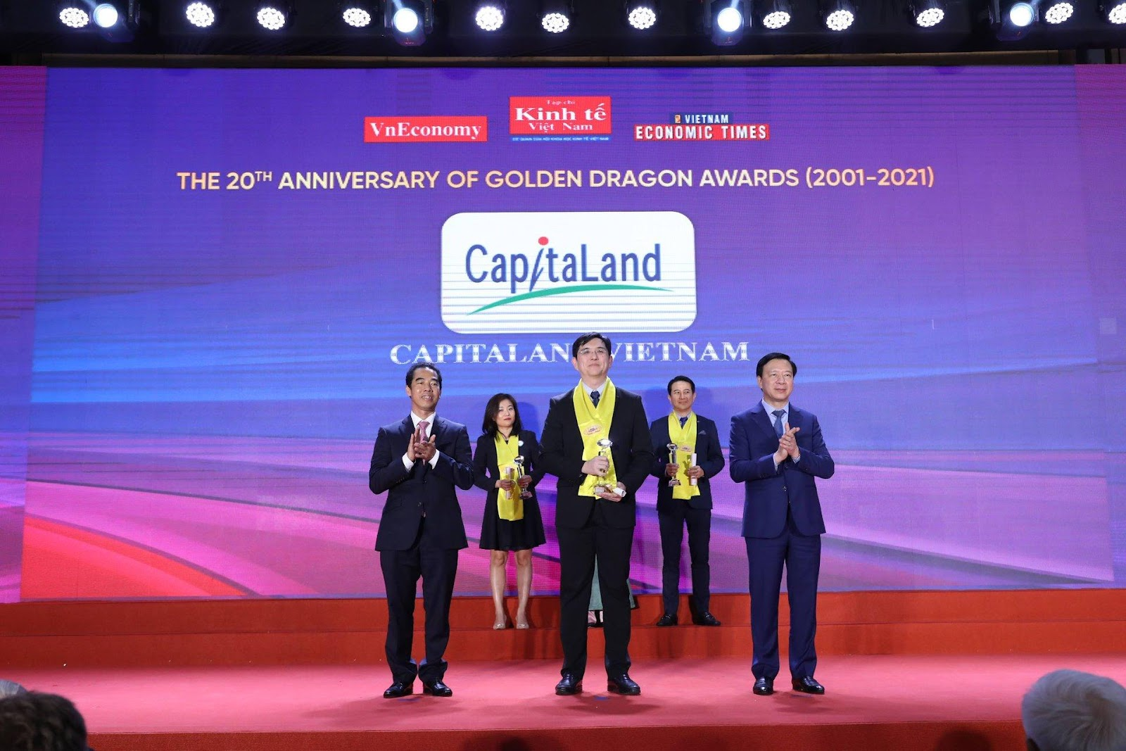May be an image of 3 people, people standing, indoor and text that says 'VnEconomy Kinh Vam VIETNAM ECONOMIC TIMES THE 20TH ANNIVERSARY OF GOLDEN DRAGON AWARDS (2001-2021) Cap/taLand CAPITALAN VIETNAM NI'