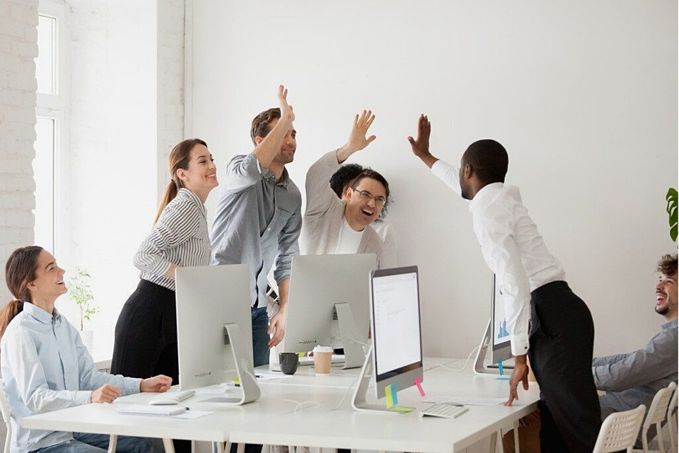 workers high fiving a successful meeting
