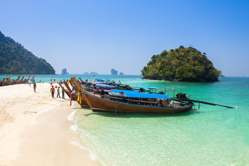6 Best Places to Visit in Asia in 2020 featured by top travel blog, The Common Traveler: image of boats on pink sand beach in Krabi, Thailand