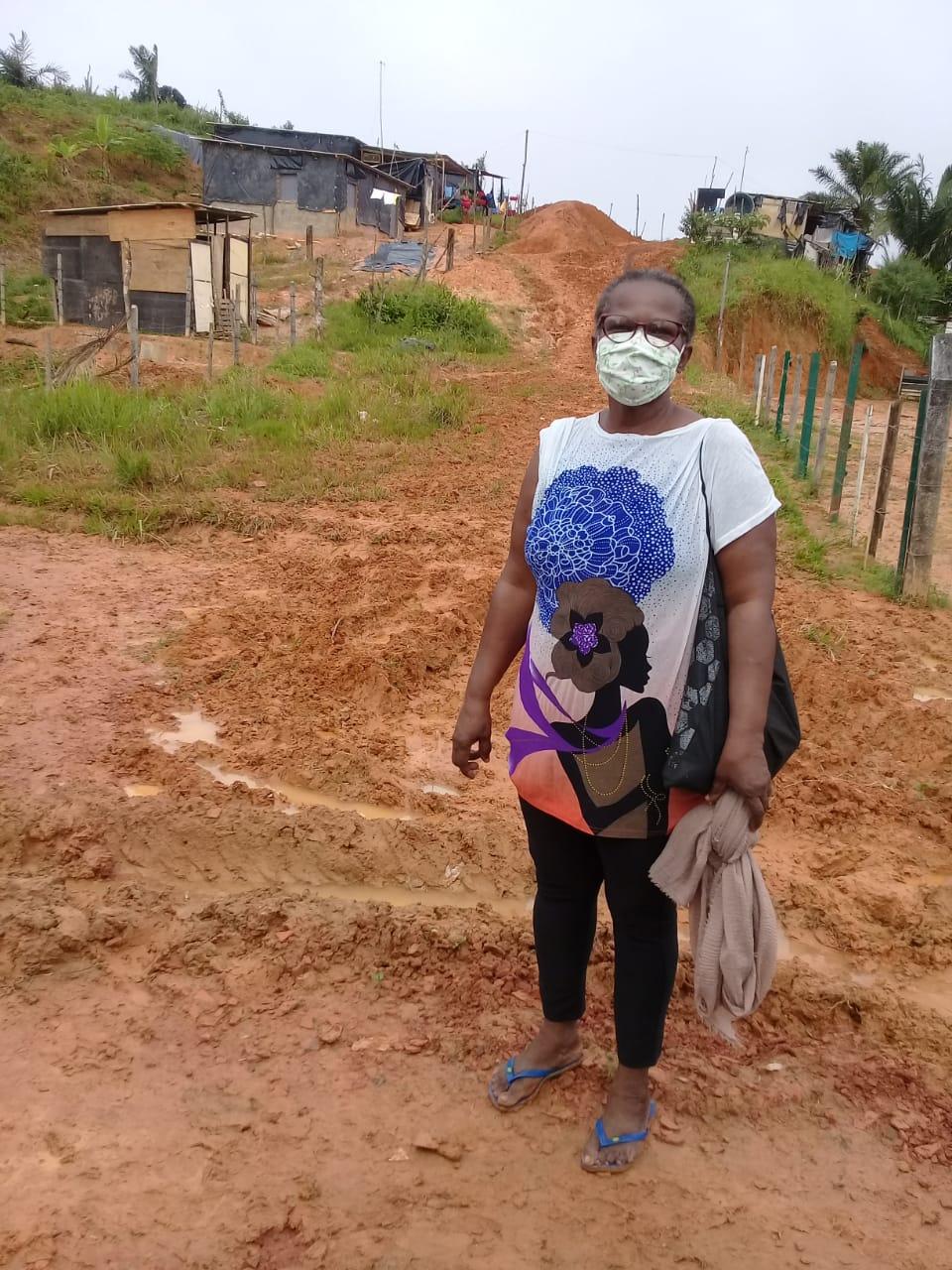 Dona Mira Alves, mulher negra, dirigente do MSTB, em pé no chão de barro de uma ocupação por moradia.