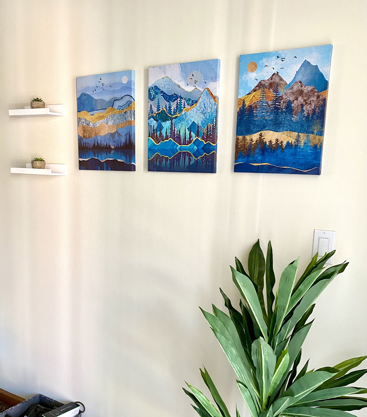 minimalist home decor featuring mountain panel paintings and plants on shelves