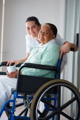 Portrait of a happy elderly woman on a wheel chair with a female nurse for assistance Stock Photo - 5841644
