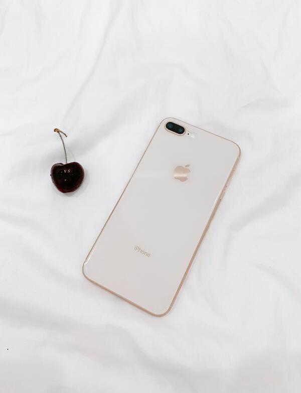 foto da parte de trás de um iphone e uma cereja