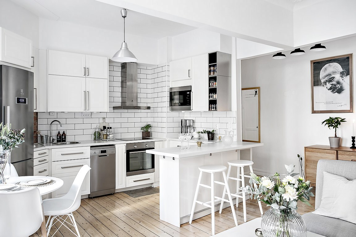 bright white apartment kitchen with all white finishes including cabients, bar stools, dining table, dining chairs and subway tile backsplash