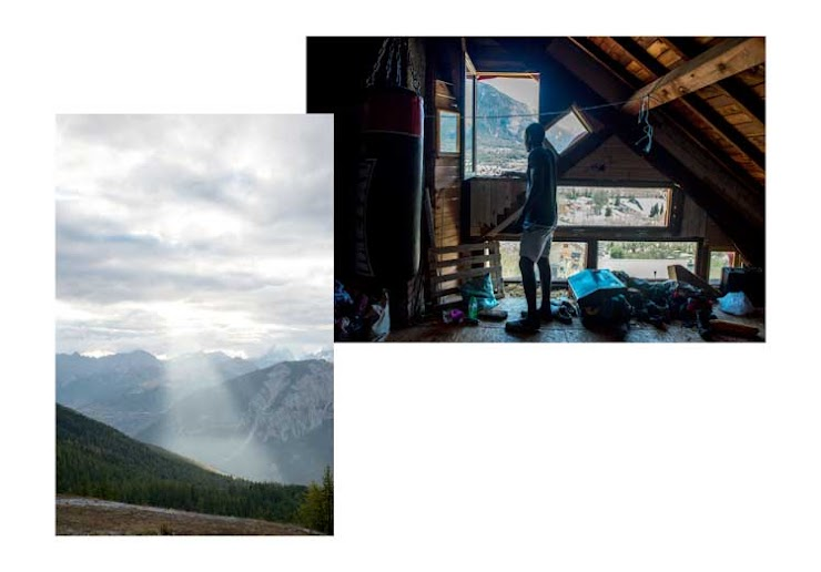 Leonel regarde le paysage montagneux à travers la fenêtre du grenier du squat de Chez Marcel, lieu d'accueil des réfugiés à Briançon. La lumière perce les nuages et éclaire la forêt entre Montgenèvre et la Vachette. France, 2018.