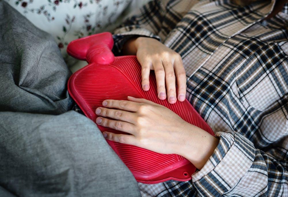 bouillote rouge sur le ventre d'une dame qui souffre