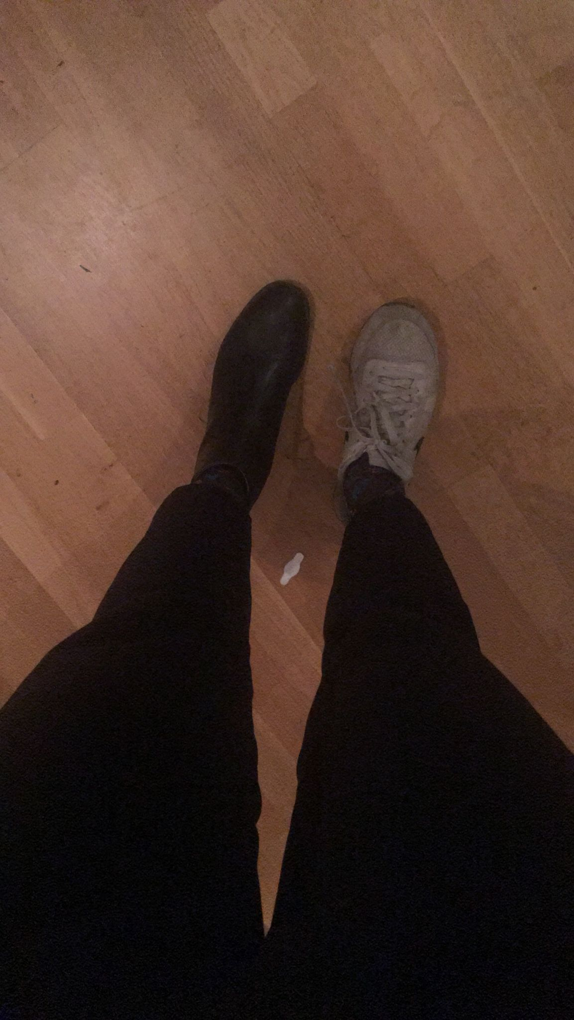 A photo of a person's legs with black pants on a wooden indoor floor.  On the left foot is a black boot, on the right foot is a white sneaker.