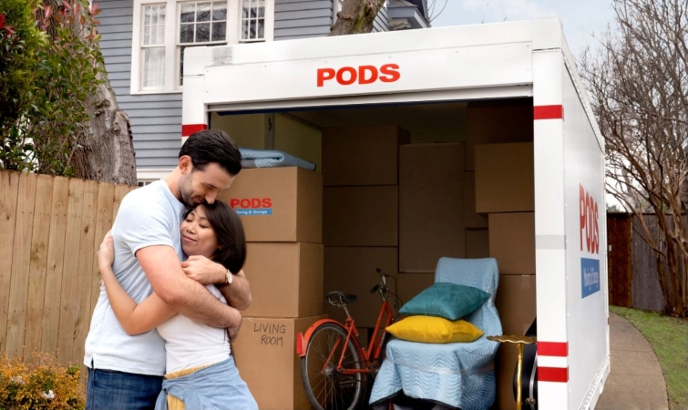 couple hugging in front of a loaded PODS moving & storage container