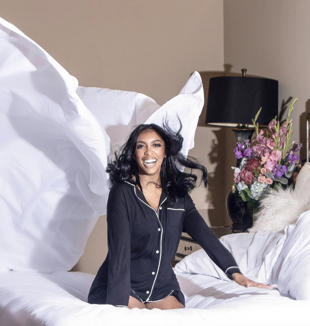 Porsha Williams laughing and bouncing on the bed