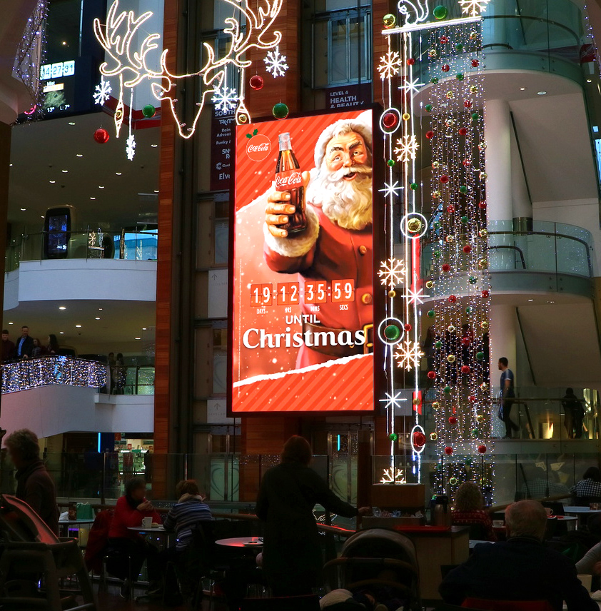 Christmas countdown Coca-Cola digital billboard with Santa Claus holding a bottle and a live countdown clock.