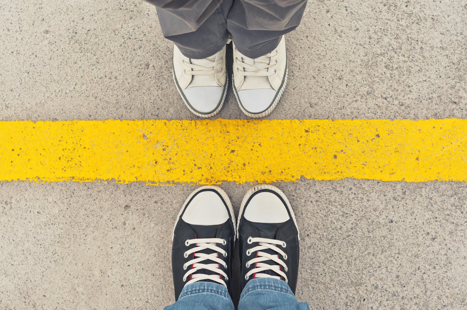 A view of looking down at shoes with another person coming up to a boundary
