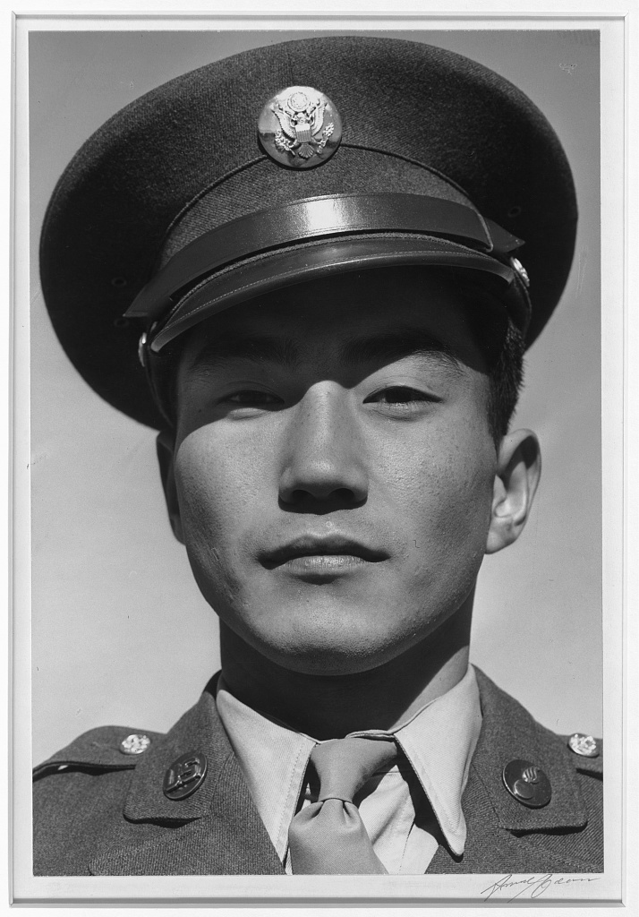 Portrait of a Japanese American soldier. He is looking at the camera with a slight smile, wearing a cap and uniform.