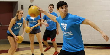 uOttawa student about to throw a dodgeball with fellow teammates in the background