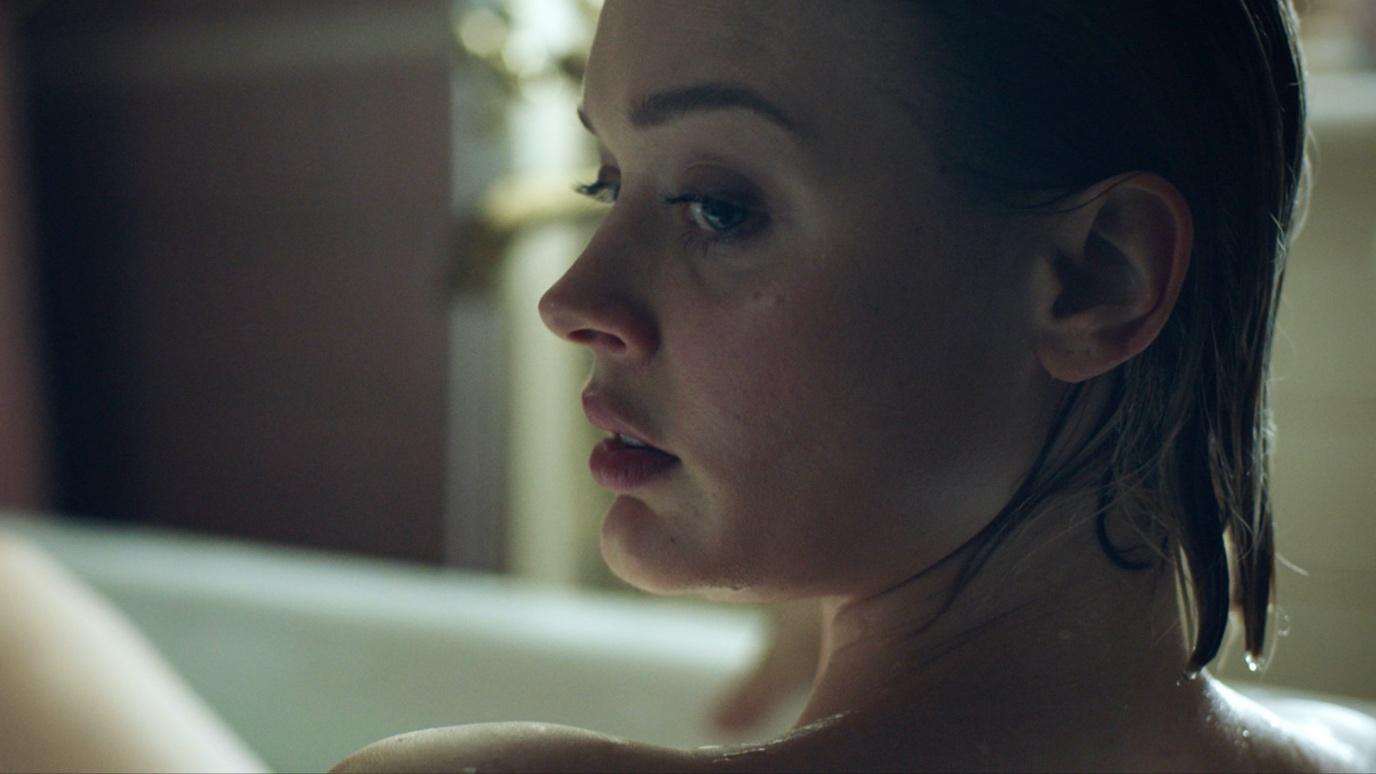 Bella Heathcote as Sam in Relic. Sam is in the bath, looking over her shoulder at something out of the frame.
