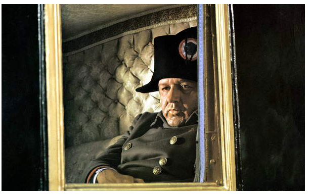 Image of a film still depicting an older Napoleon staring out of a carriage window with a contemplative gaze, Napoleon is here played by actor Rod Steiger © Dino de Laurentiis Cinematografica/Mosfilm / Collection CSFF / Bridgeman Images