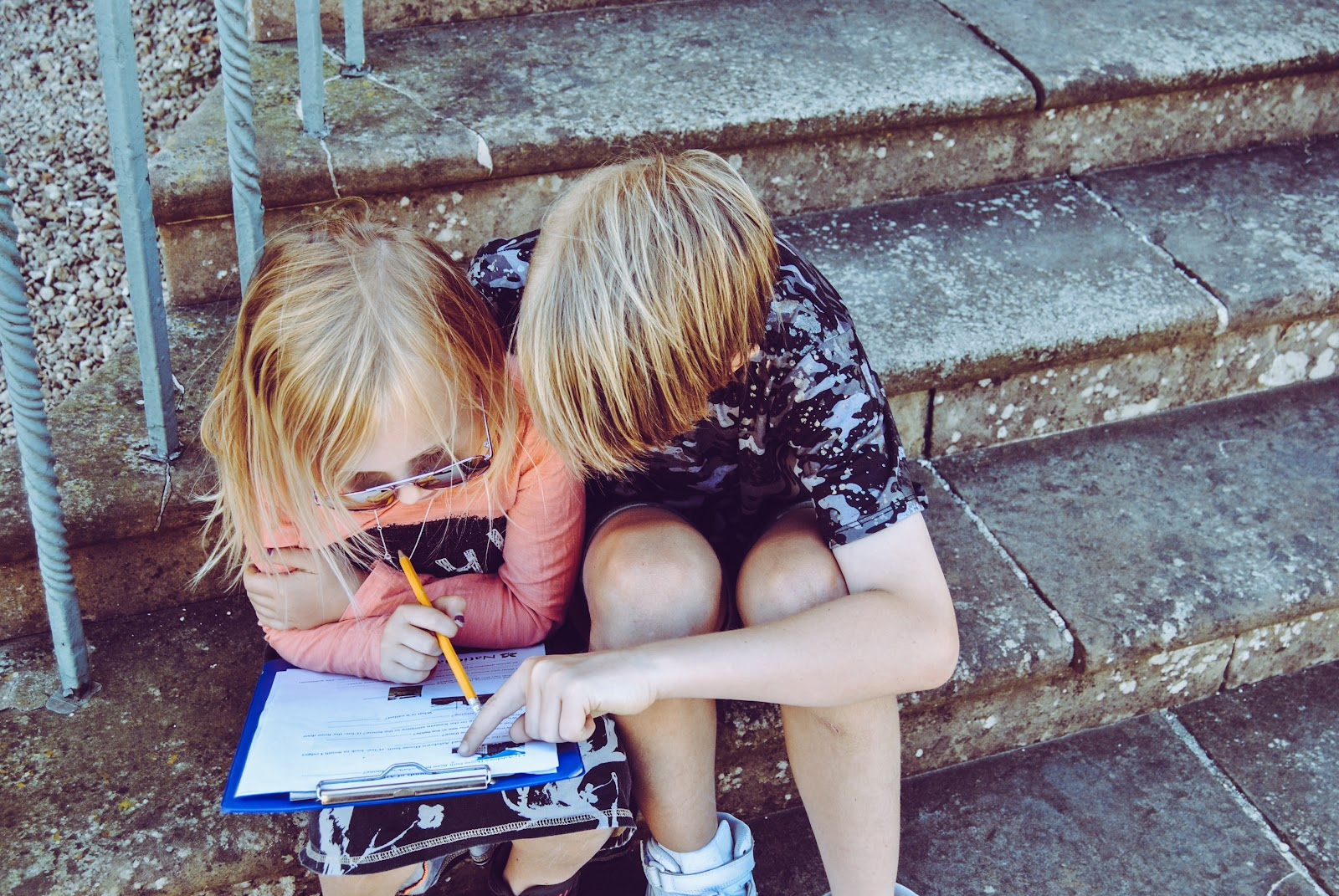 two children doing schoolwork on porch steps shelter in place working together family ideas