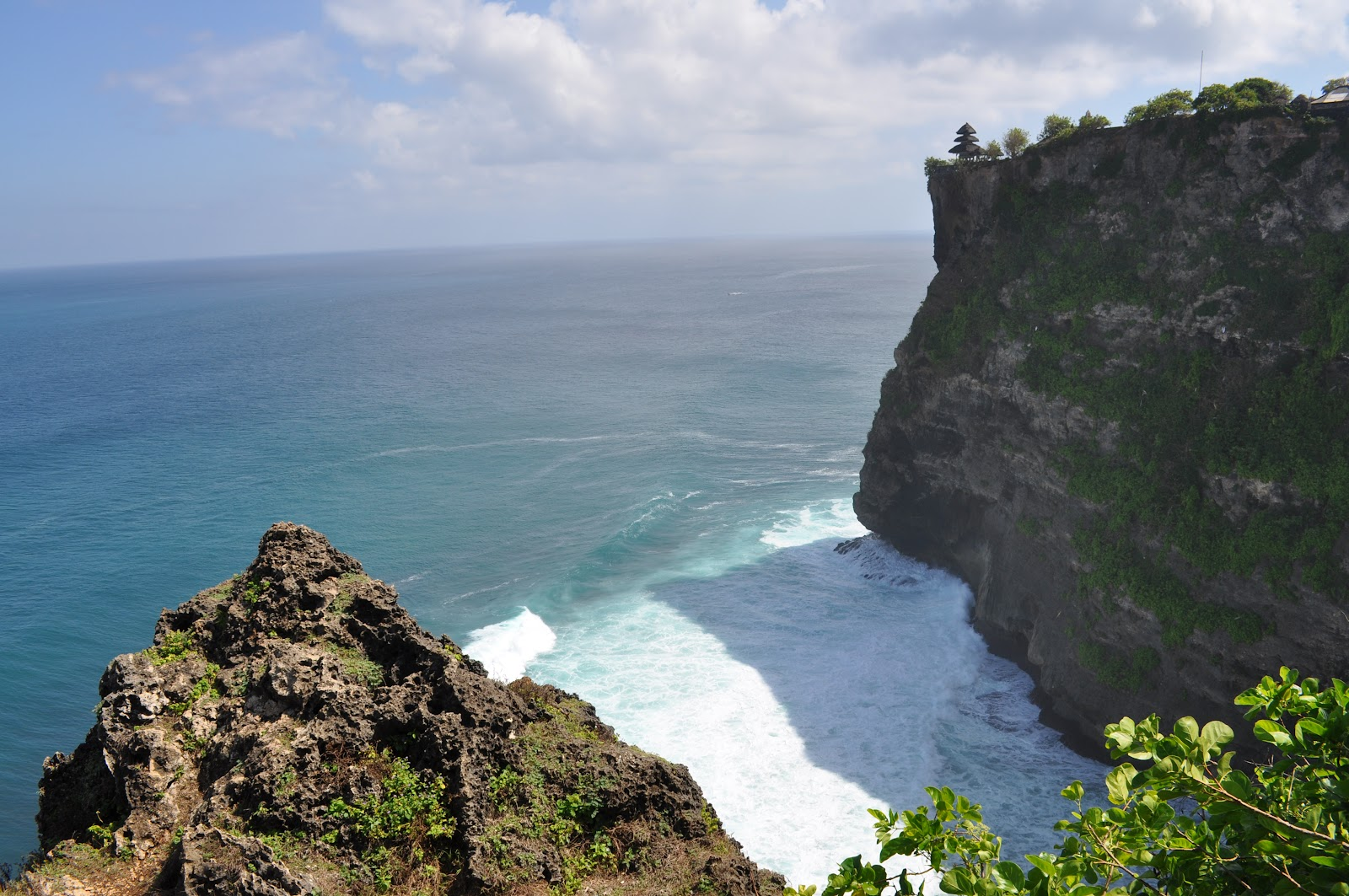 south bali buddhist temple on the edge of tall cliff overlooking blue ocean waves and green grass on a sunny day