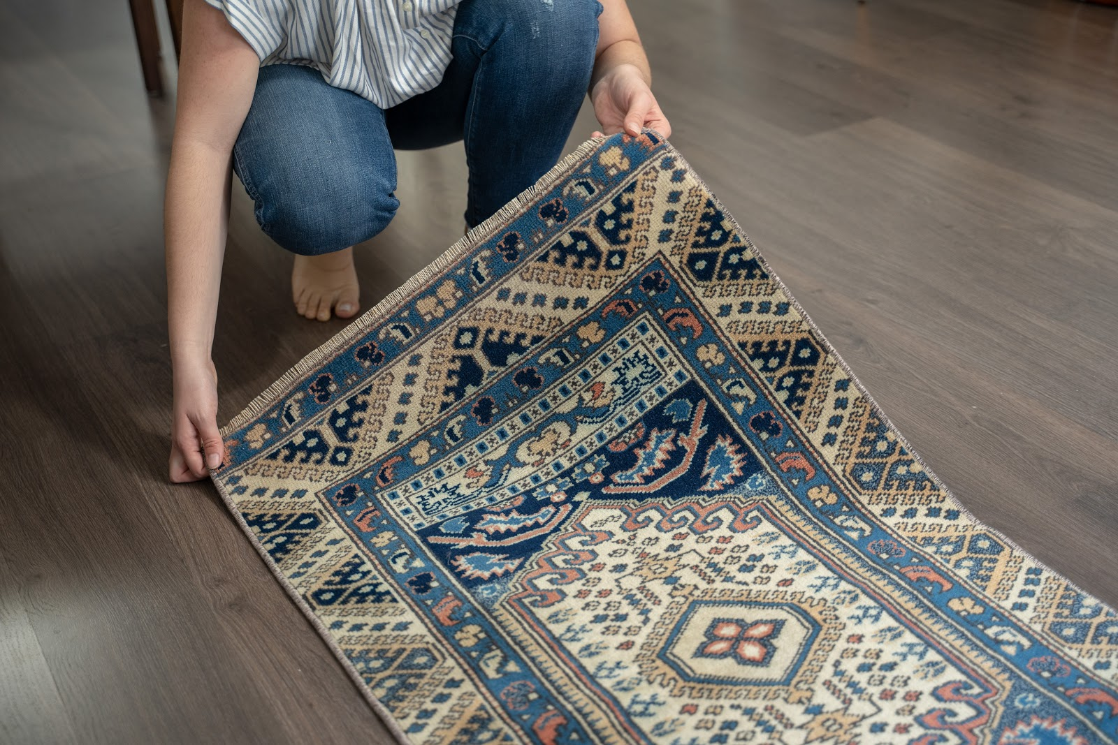 Image of a vintage rug being shown by a person on a wooden floor.
