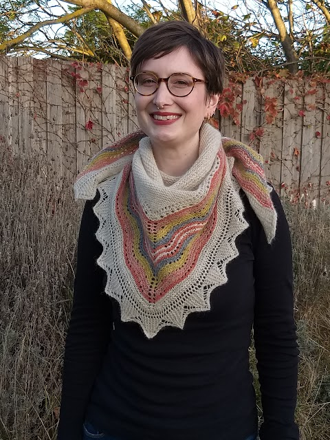 Siobhan stands against a garden fence. She wears a triangular handknit shawl wrapped around her neck; in beige with red, orange, yellow and grey/blue coloured lace stripes.
