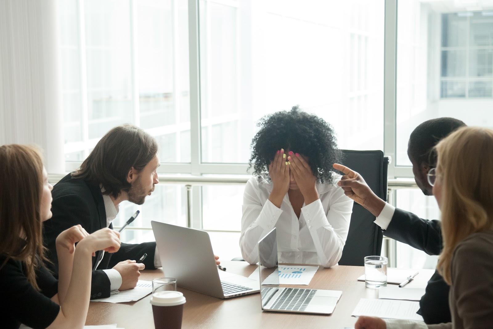 Uma mulher frustrada e seus colegas de trabalho gritando com ela.