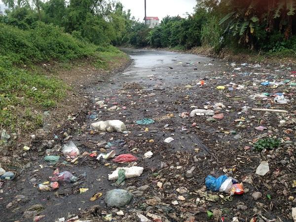rác thải, váng chất thải ứ đọng nổi lềnh bềnh dưới con kênh.