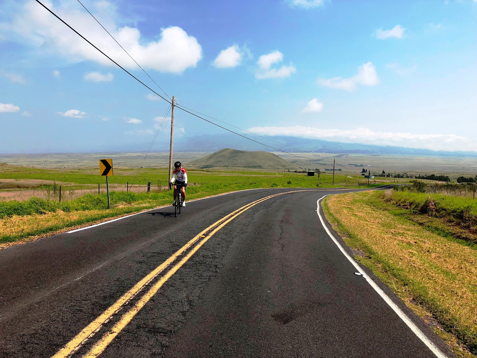 Cimbing Mauna Loa Volcano by bike - cyclists on old saddle road with cinder cone in background