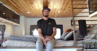 man on his bed in ambulance tiny home