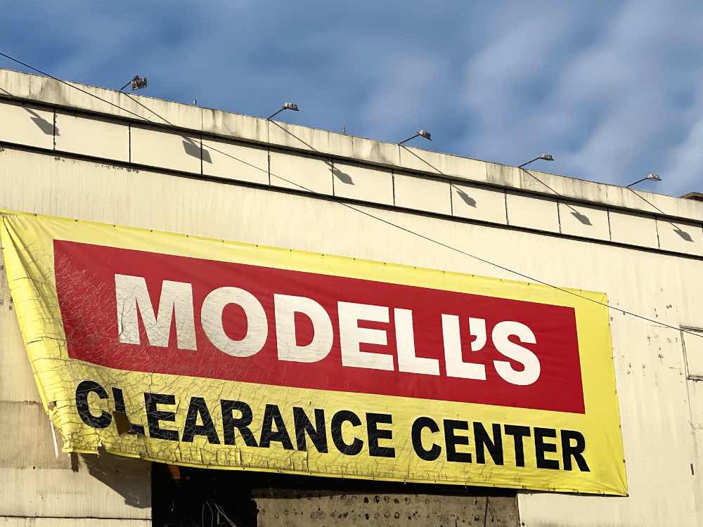 A flapping Modell's Clearance Center sign