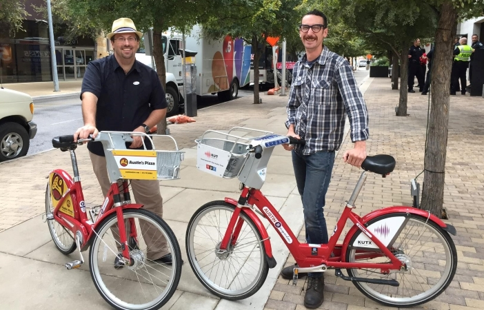 two men stand with Austin's MetroBikes in Austin, TX