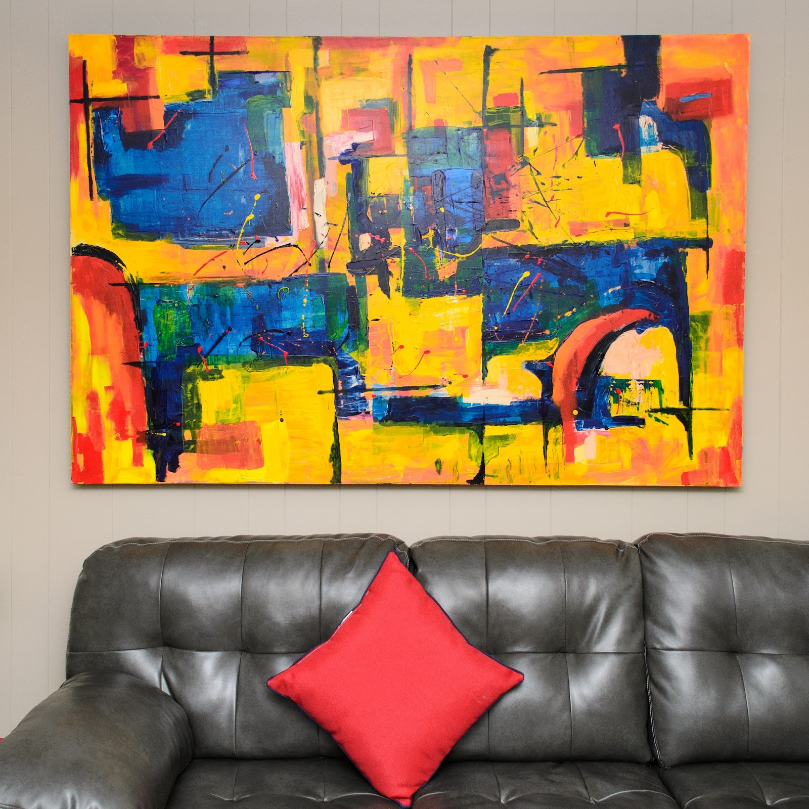 condo unit with a brown leather couch and a red pillow with a vibrant abstract painting hung on the wall of a condo unit space