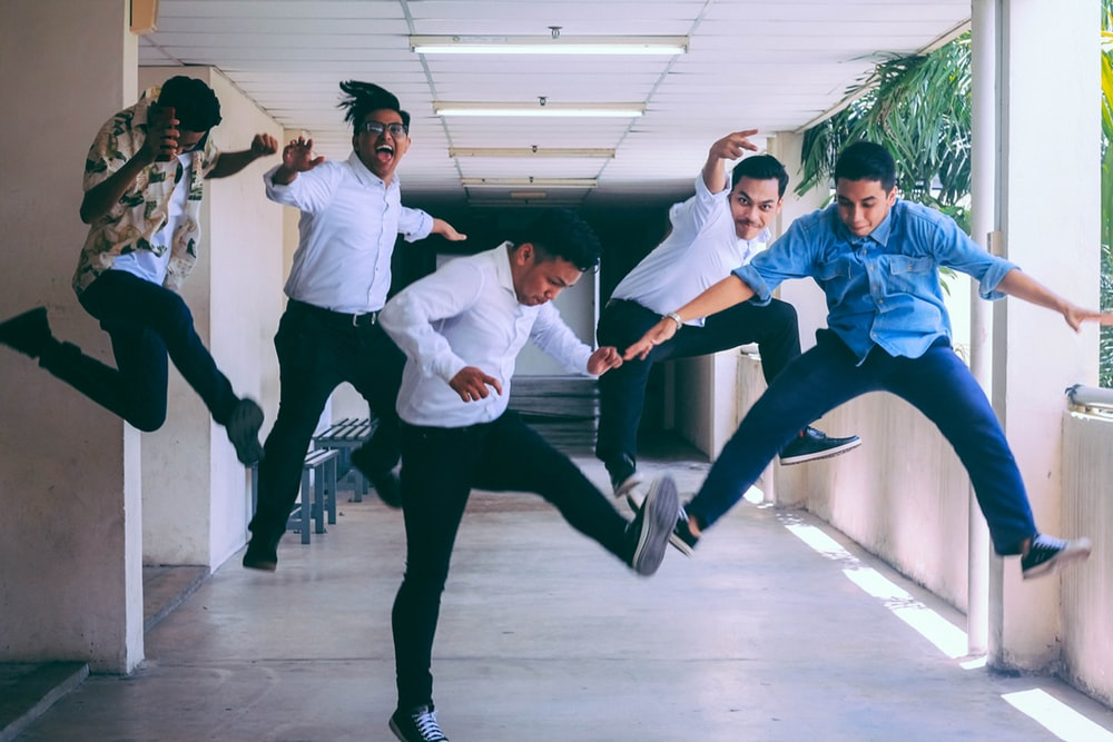 group of people doing jump after hearing benefits to offer employees