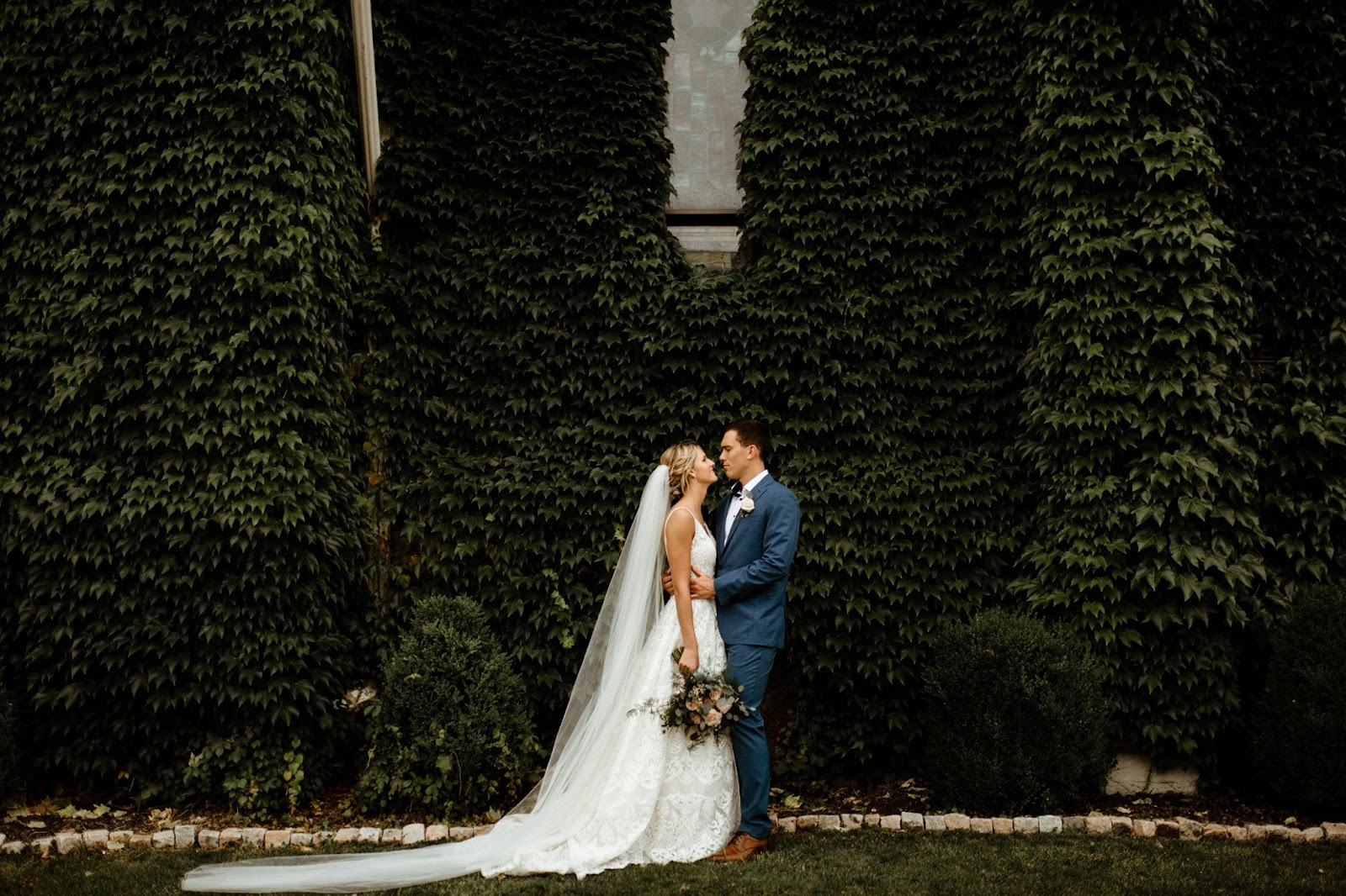 small wedding venue couple in front of green vines and brick structure