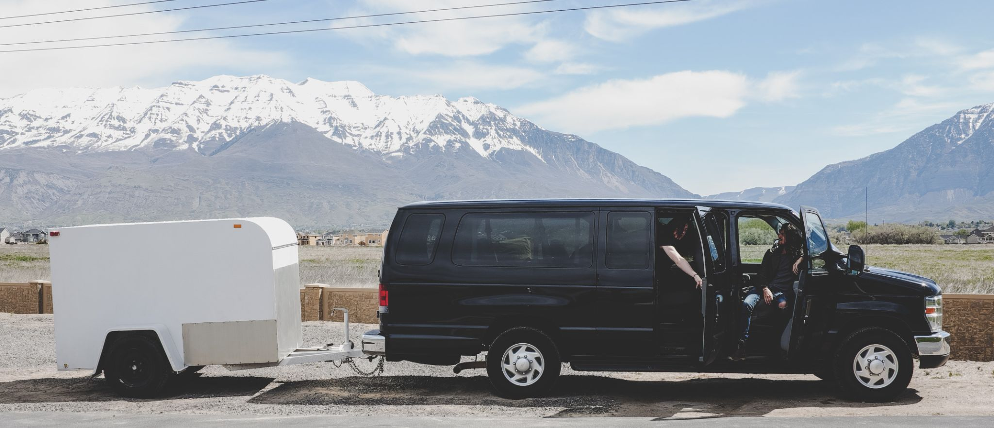 Large van with open doors with a small white trailer attached in front of some mountains