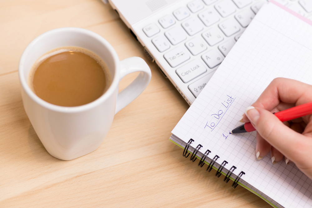woman making a to do list with coffee next to her