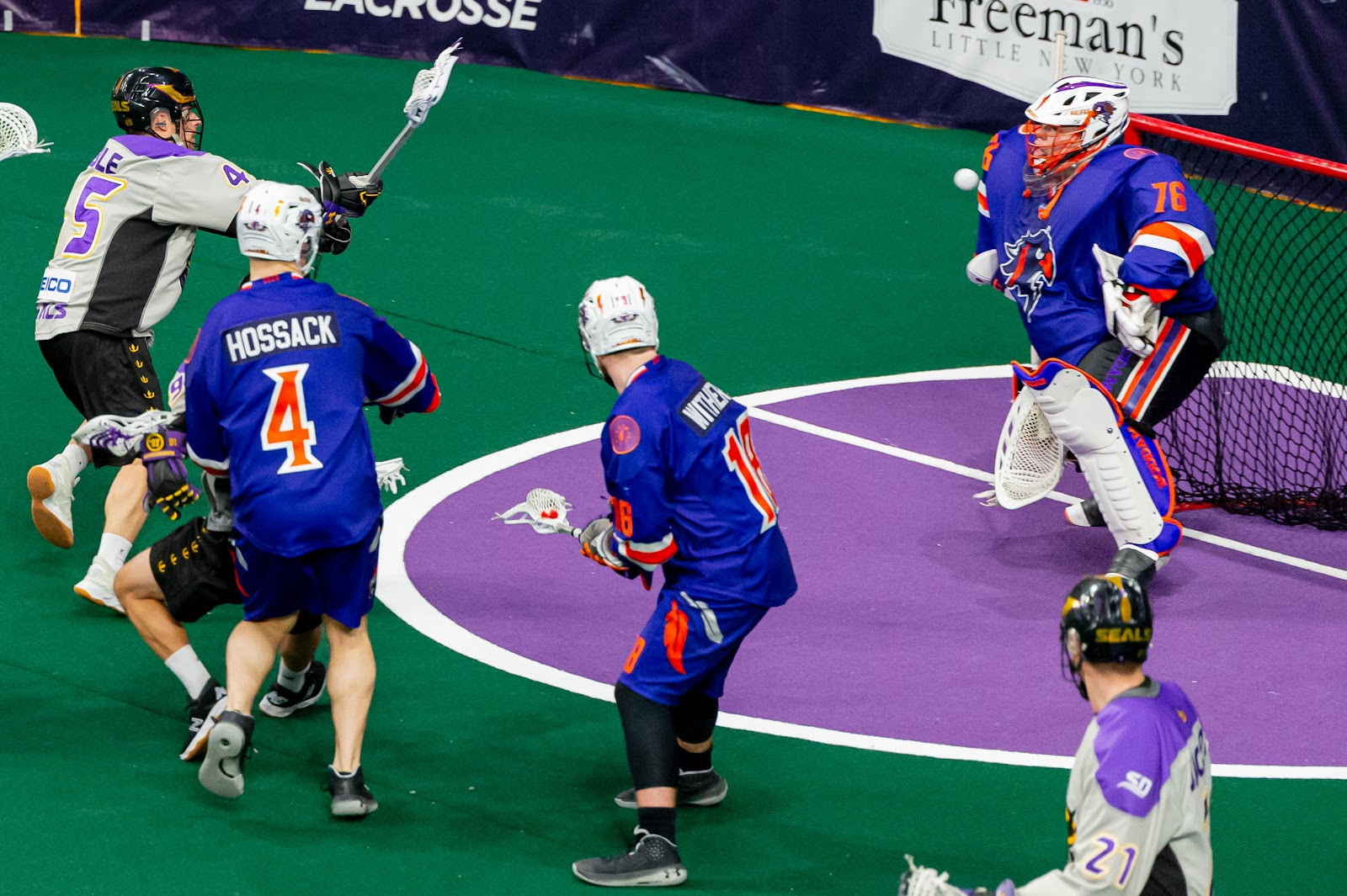 Image of goalie standing up to the ball as it is shot on net