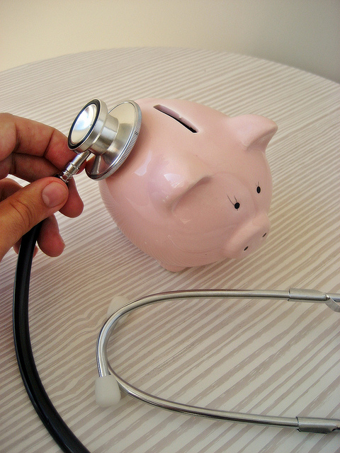 Using stethoscope on pink piggy bank