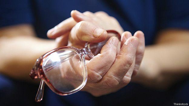Сжимая очки в руках