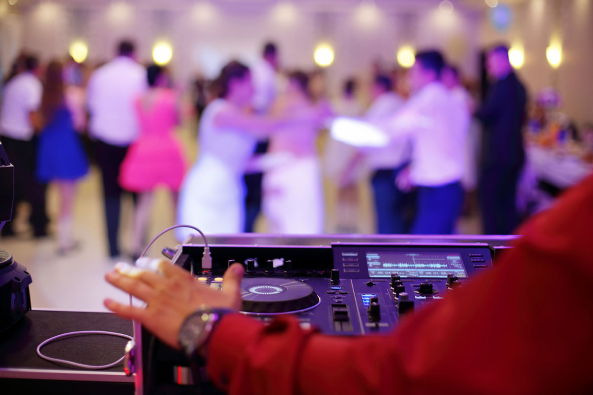 Man DJing while dancing couples party at wedding celebration