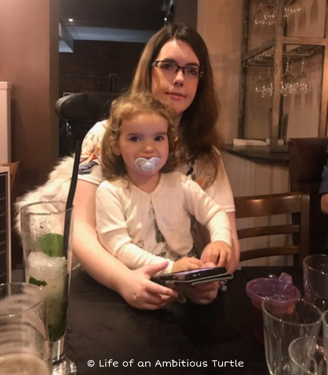 Photo of me at the table, Ava on my lap both wearing nice smart casual attire during surprise family meal at the restaurant