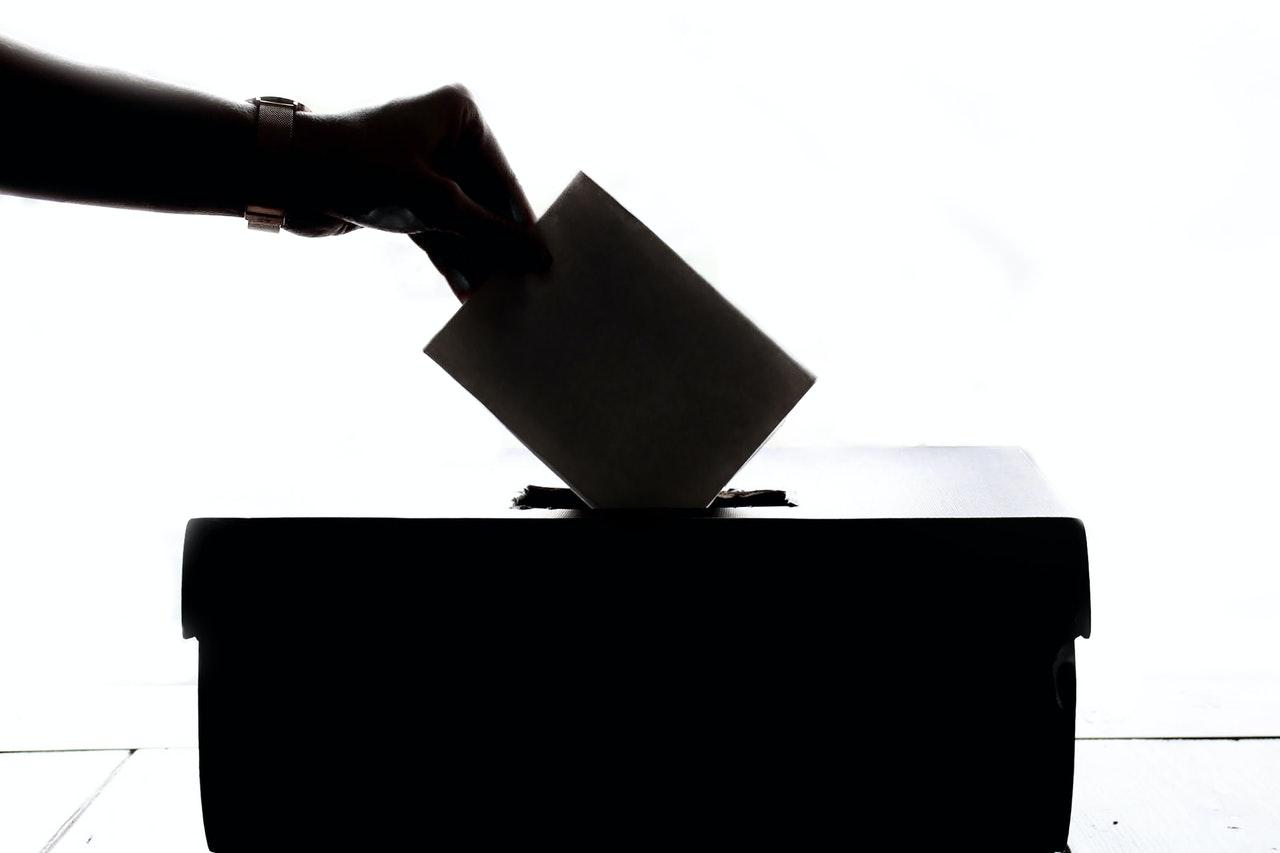 Czarno-białe ujęcie skrzyni wyborczej z ręką wrzucającą kartę do głosowania