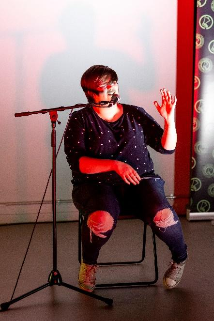 Image description: Katie Walters is performing against a white walled background, whilst seated with their left arm raised. Katie is seen to be speaking into a microphone and wearing worn pumps, torn jeans and a dark jumper with white dots. Katie has cropped hair that is swept across the forehead.