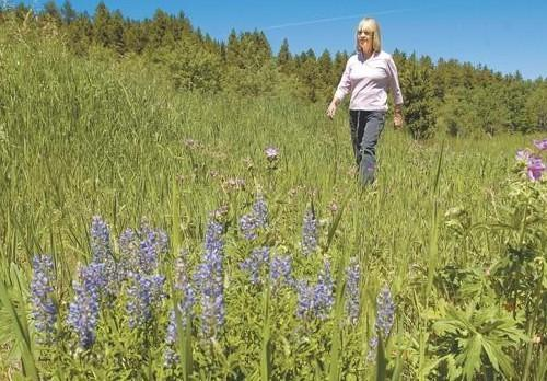 A person standing on top of a grass covered field  Description automatically generated