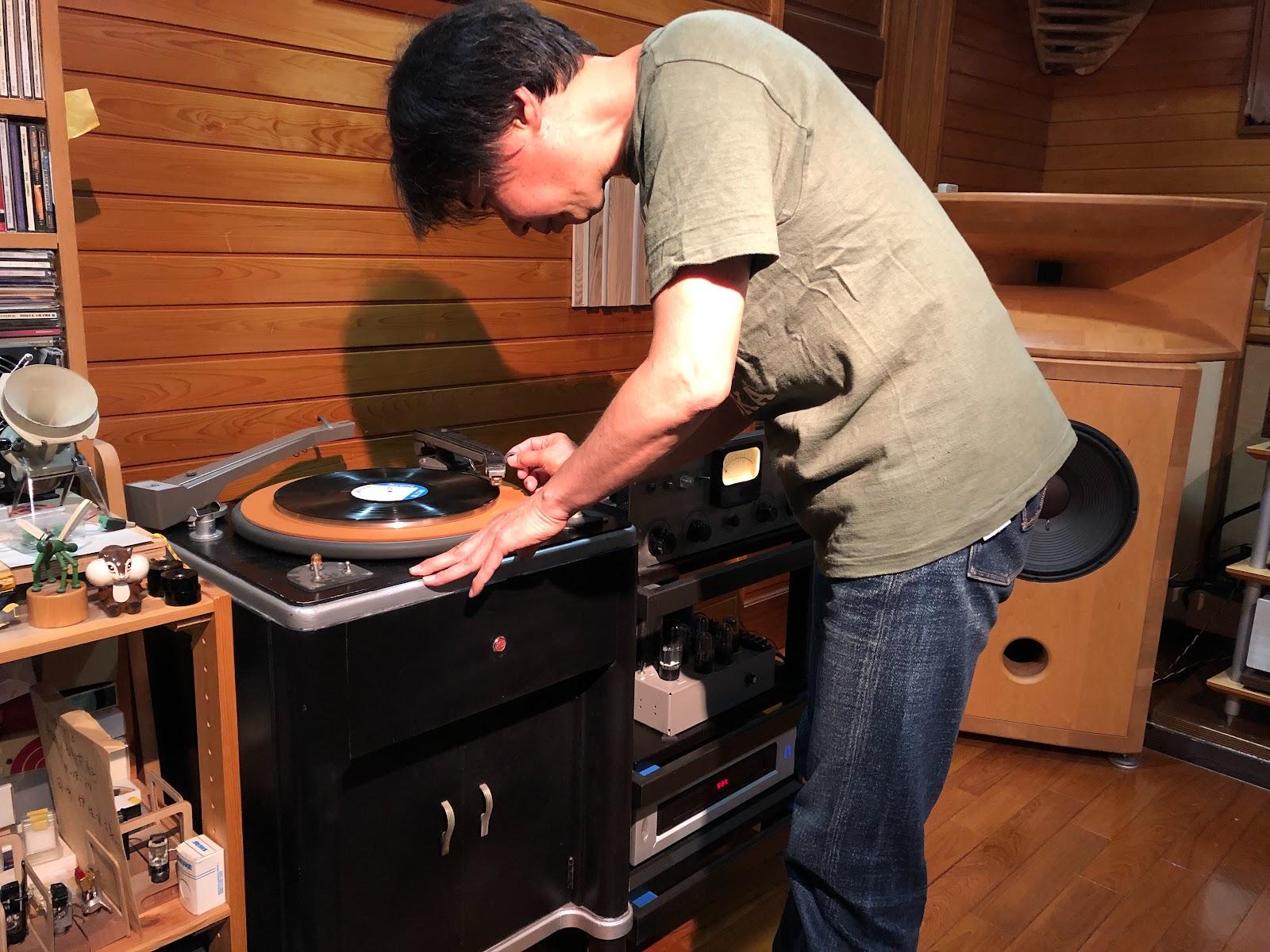 モノラルプレーヤーでレコードをかける田中氏