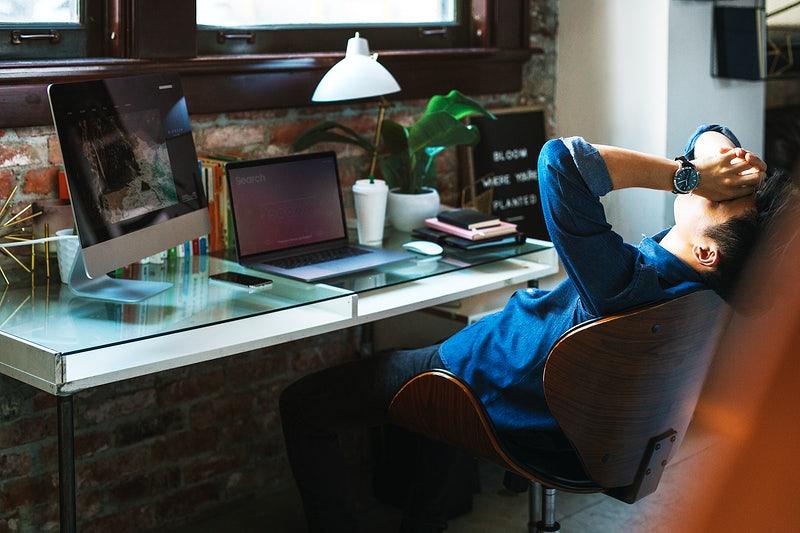 Um homem frustrado com algo do trabalho em uma mesa.