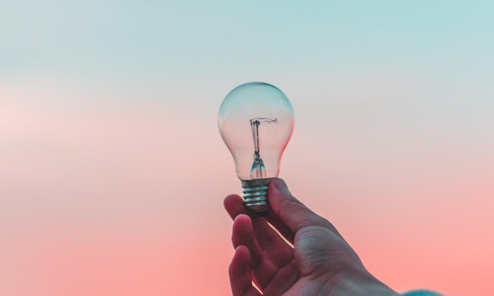 Pessoa segurando uma lâmpada no pôr do sol, dando ideia de criatividade e inovação que uma pessoa pode ter com ela