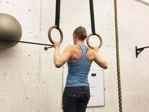 一個女子正在做引體向上的背影。