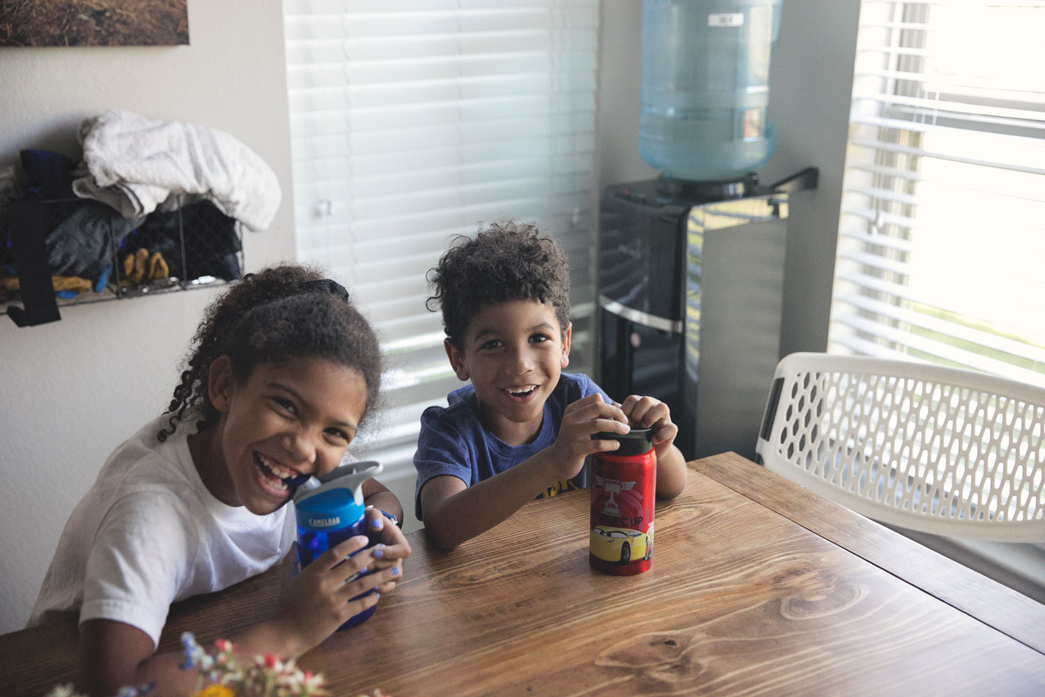 Biracial siblings laughing while sitting at the kitchen table in front of their Primo water dispenser.