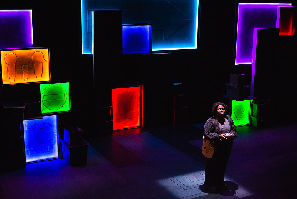 A student actor stands on stage with colorful and brightly lit rectangles behind her.